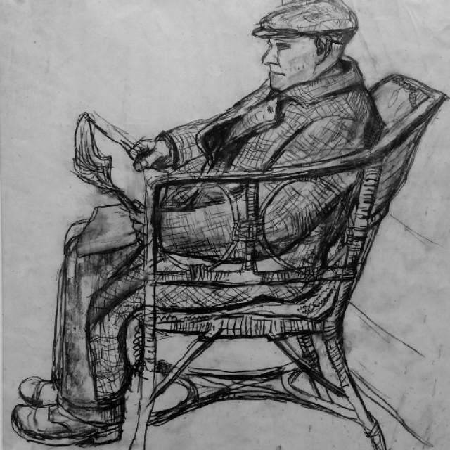 Man in wicker chair, reading